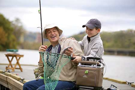 man fishing with son with portable oxygen system